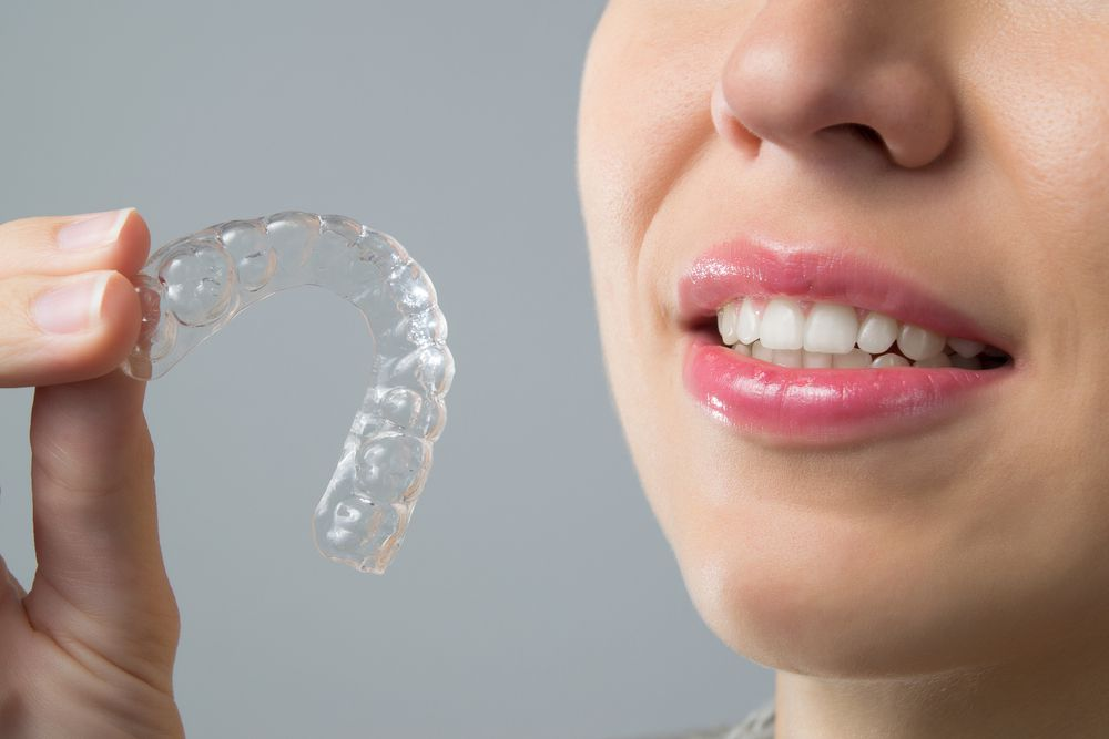 Smiling girl with Invisalign in hand