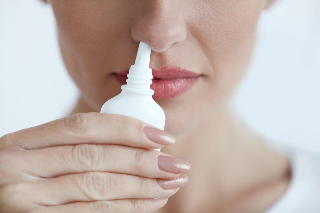 Closeup of a woman holding a nasal spray container in her nose