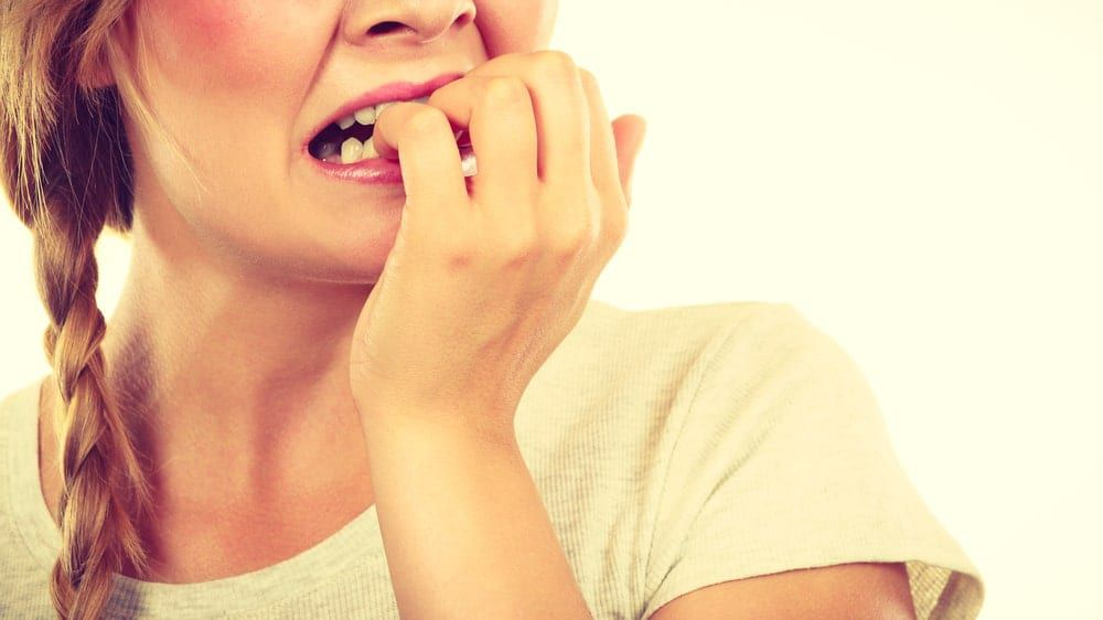 Closeup of a woman with anxiety biting her nails