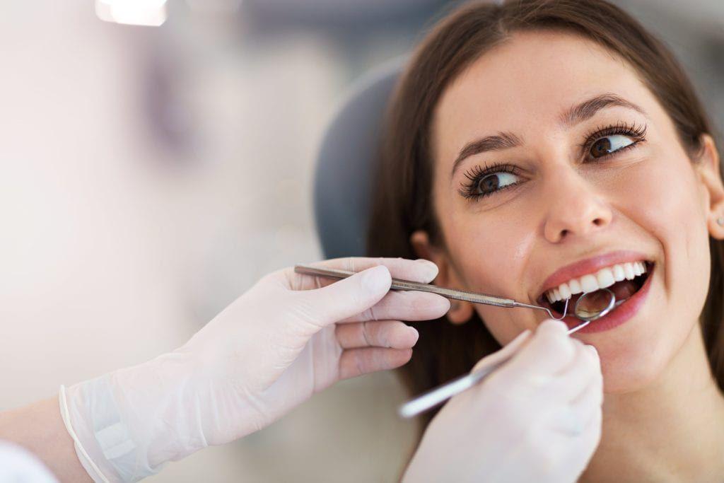 Woman having her teeth examined