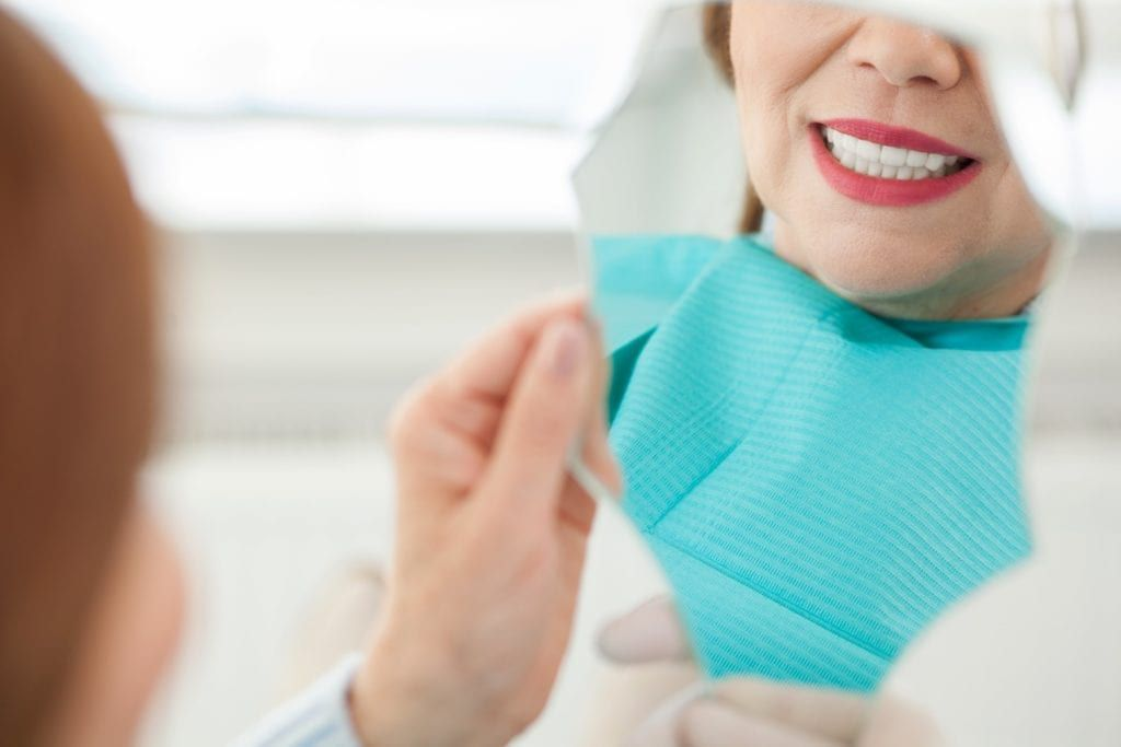 Older woman looking in the mirror after dental work