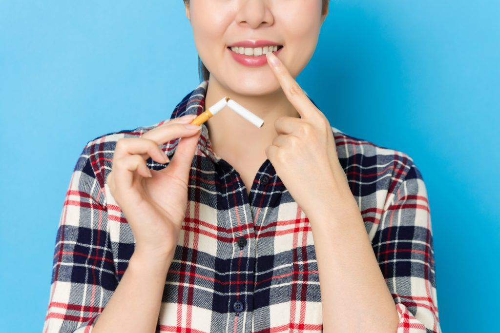 woman holding cigarette and pointing to her teeth