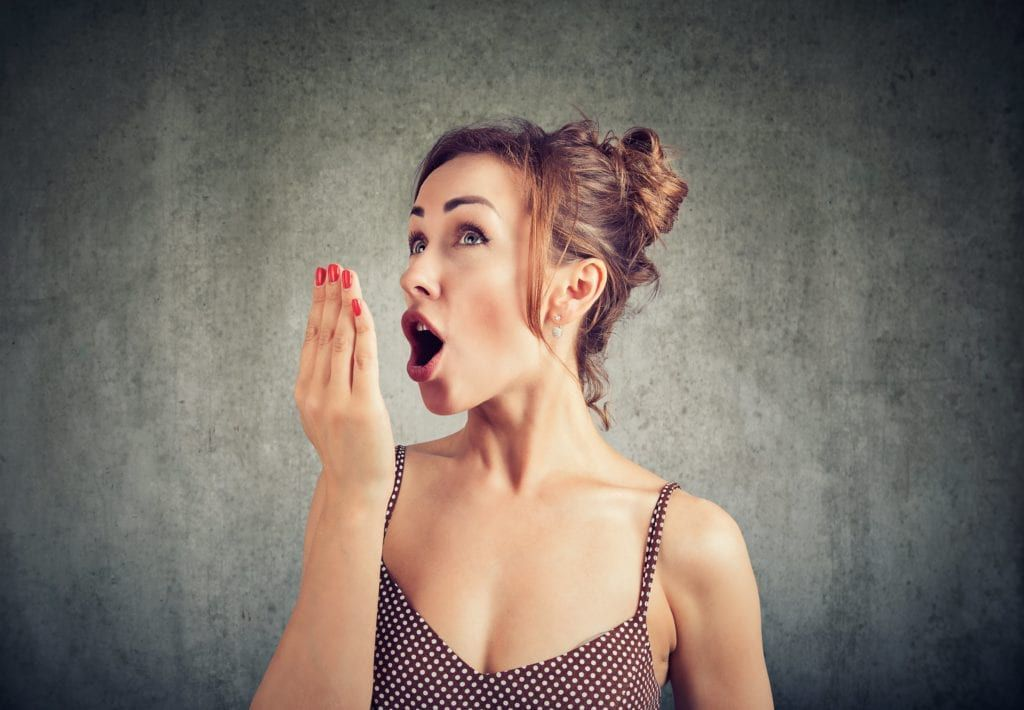 woman holding her hand in front of her mouth and testing her breath