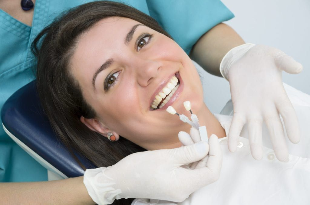 woman being color matched for teeth whitening