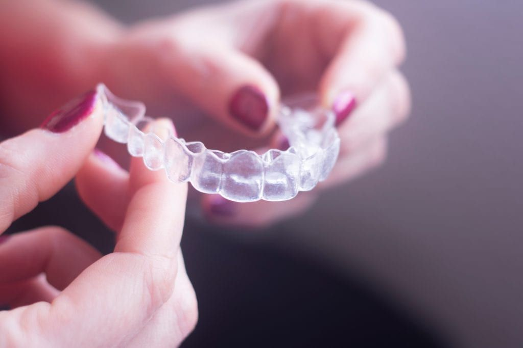 female hands holding clear aligners