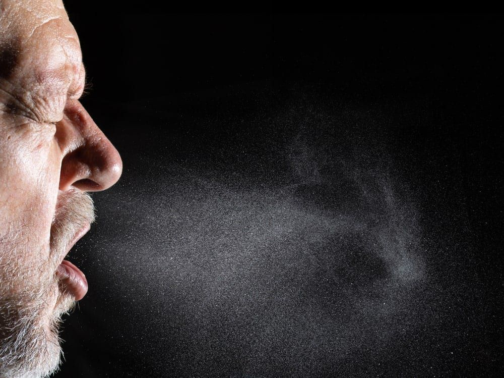 man exhaling airborne droplets