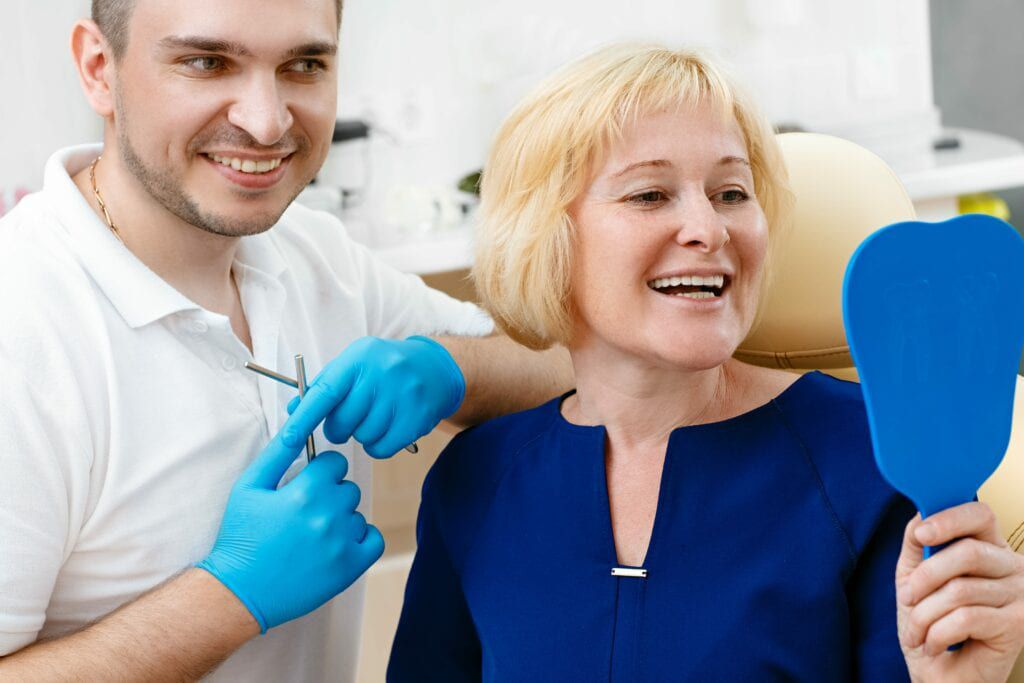 woman looking in mirror at dentist office