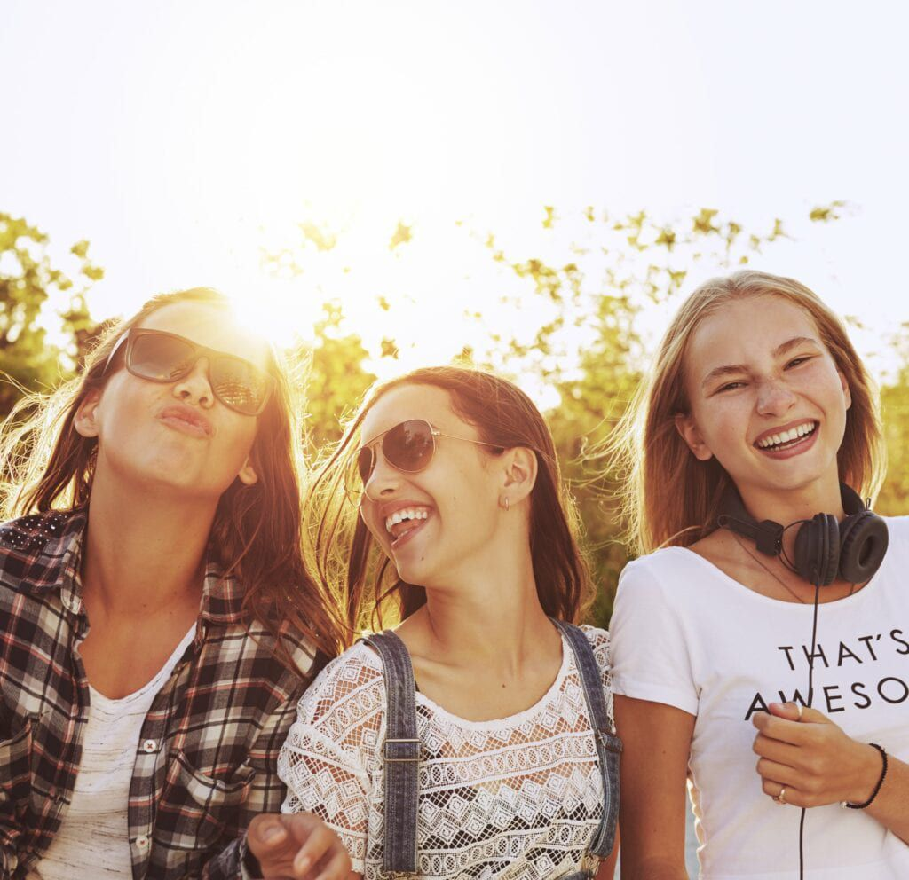 three teenage girls laughing